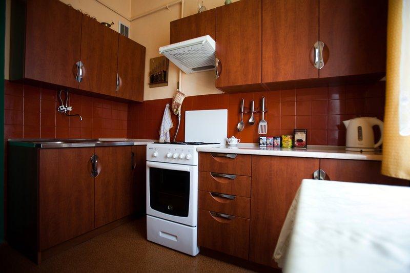 Zabudowa kuchenna z frontami drewnopodobnymi z wgłębieniami na uchwyty chromowane
