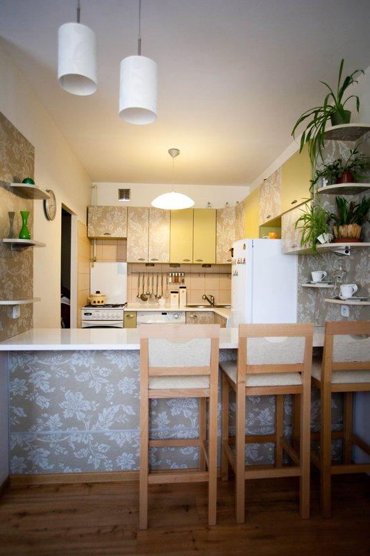 Kuchnia w bloku NRD barkiem i wysokimi krzesłami oddzielającymi kuchnię od pokoju